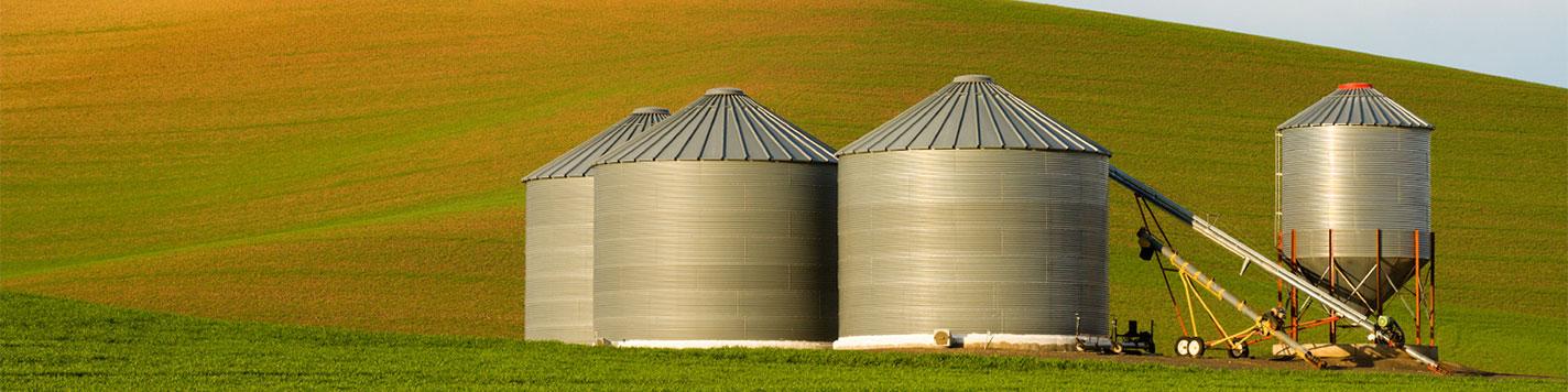 A grain bin and agriculture equipment set against a green field.